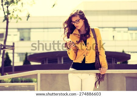 young urban woman with eyeglasses using smartphone,  outdoor shot in the city, retro colors - stock photo