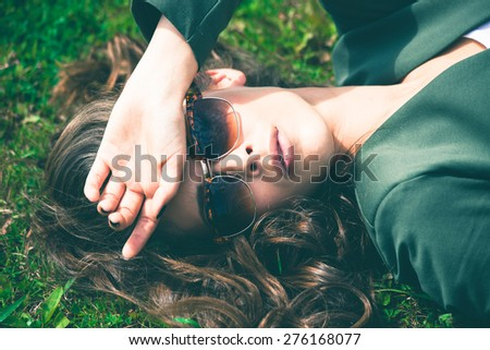 young  urban woman with sunglasses lie in grass,  retro colors - stock photo