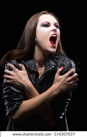 Young vampire girl isolated on black - stock photo