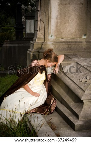 Young victorian woman in mourning in a cemetery - stock photo