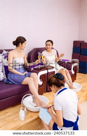 Young Vietnamese girls talking and drinking champagne during pedicure procedure - stock photo
