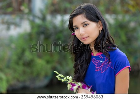 Young Vietnamese woman in blue Ao Dai holding flowers while Looking at the Camera. - stock photo