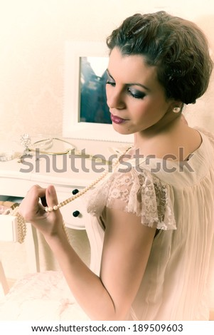 Young vintage 1920s woman choosing jewelry in her boudoir - stock photo