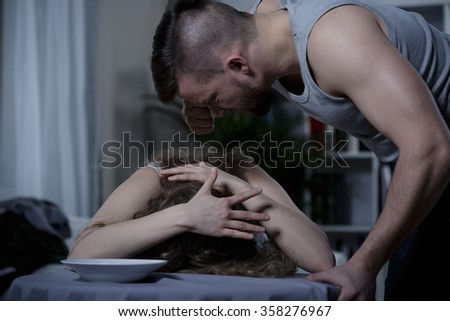 Young violent man yelling at scared woman - stock photo