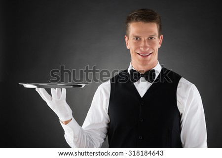Young Waiter Holding Silver Tray In Hands - stock photo