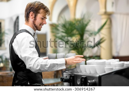 Young waiter serving coffee cups on the coffee machine - stock photo