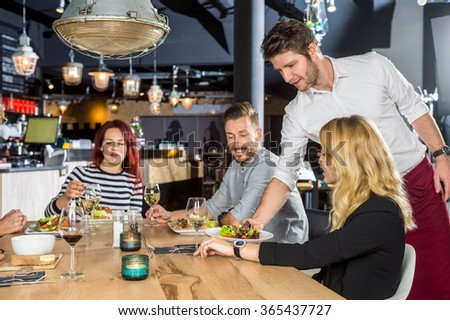 Young waiter serving food to customers at table in cafe - stock photo