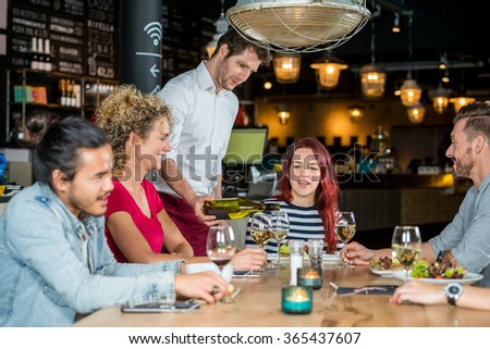 Young waiter serving wine to customers at table in restaurant - stock photo