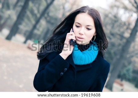 Young walking woman talking on mobile phone. - stock photo