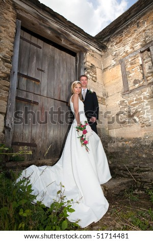 Young wedding couple against a grunge medieval wall - stock photo