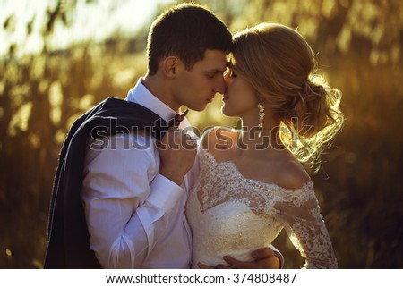 young wedding couple, beautiful bride with groom portrait on the sunset near the ears of wheat, summer nature outdoor - stock photo