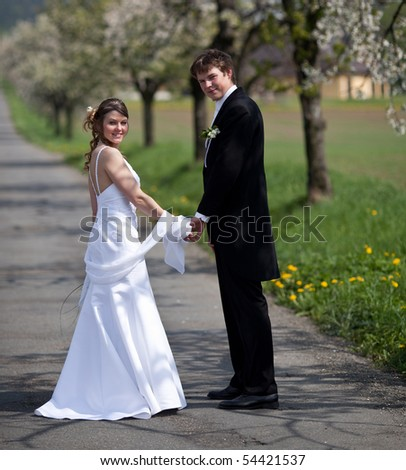 young wedding couple - freshly wed groom and bride posing outdoors on a lovely spring day - stock photo