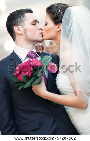 Young wedding couple kissing. Bright white colors. - stock photo