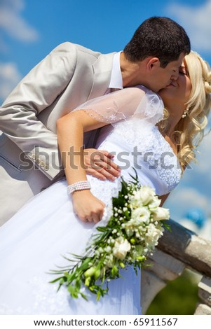 Young wedding couple kissing. Camera angle view. - stock photo