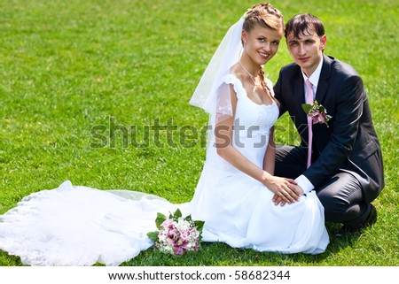 Young wedding couple on green grass - stock photo