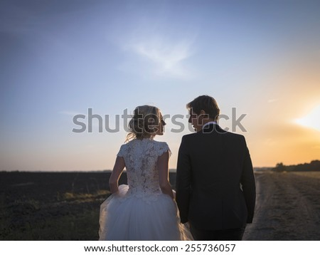 Young wedding couple talking on the field at sunset. Newlyweds back to Kemer look at each other. - stock photo