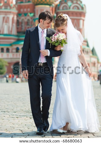 Young wedding couple walking on Red Square. - stock photo