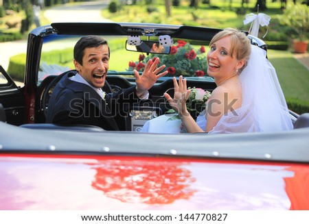 Young wedding couple waving in cabriolet car - stock photo