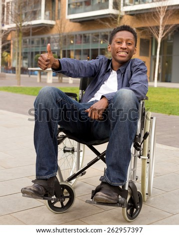 young wheelchair user showing the thumbs up symbol - stock photo