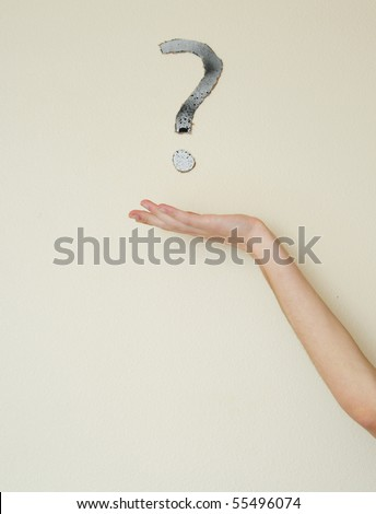 Young white Caucasian male wondering with a question mark above his head on the wall behind him. Focus point is on the person. - stock photo