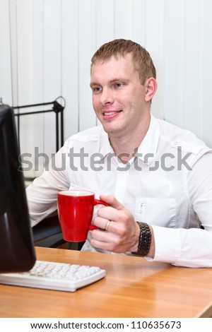 Young white collar worker with red mug in hand at working place - stock photo
