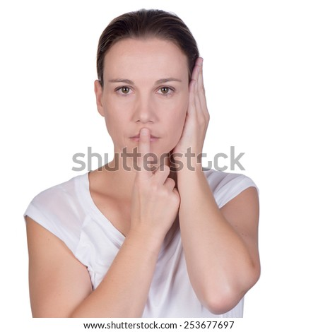 Young white deaf or hearing impaired woman holding her hand over her ear and one finger on her lips - stock photo