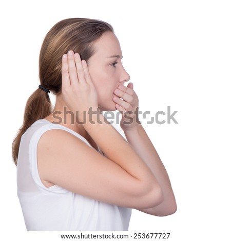 Young white deaf or hearing impaired woman holding her hand over her ear and one hand over her mouth - stock photo