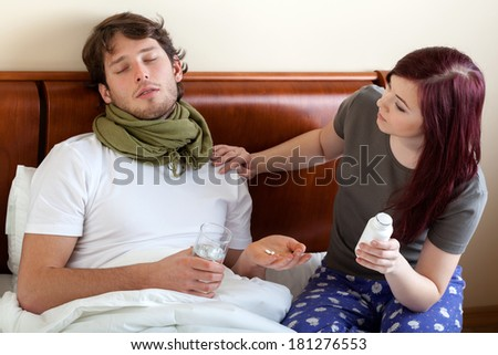 Young wife looking after her ill husband - stock photo
