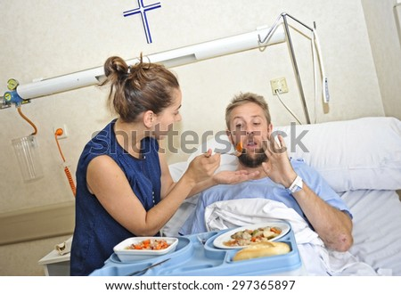 young wife trying to feed his husband lying in bed at hospital room ill after suffering accident and him looking unhappy with the diet food at the clinic center rejecting the meal - stock photo