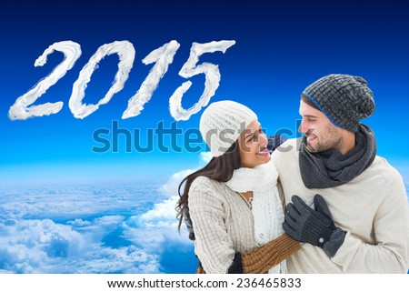 Young winter couple against mountain peak through the clouds - stock photo