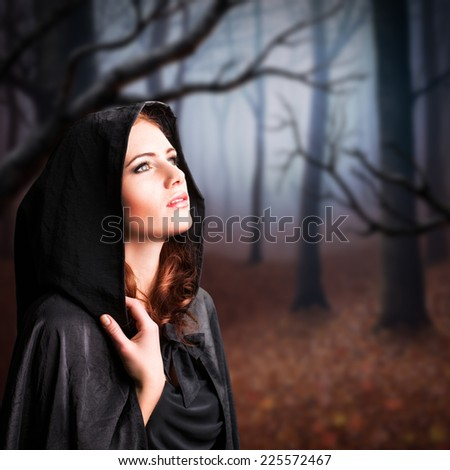 young witch in a forest - stock photo