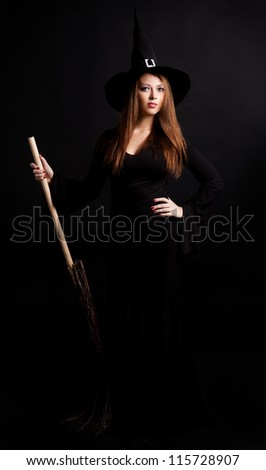 young  witch with  a broom, against dark studio background - stock photo