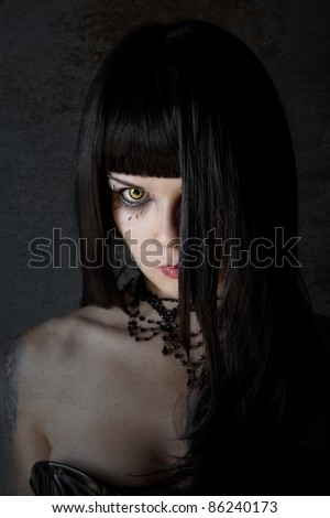 Young witch with yellow eyes and black long hair, textured background - stock photo