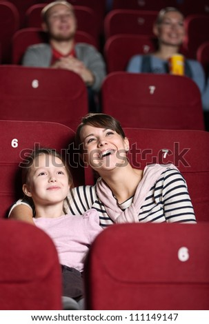 Young with her mother watching a movie at the cinema - stock photo