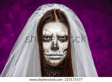 Young woman a bride in a veil on the day of the dead mask skull face art. Halloween face art. - stock photo