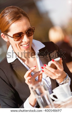 Young woman accessing business social network over smart phone - stock photo