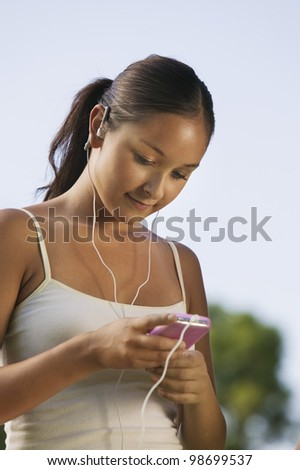 Young Woman Adjusting MP3 Player - stock photo