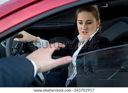 Young woman afraid of burglar trying to break into the car - stock photo
