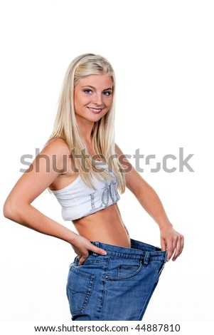 Young woman after a successful diet with large trousers: - stock photo