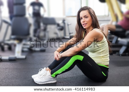 Young woman after exercising in a gym is looking at the camera - stock photo