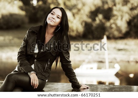 Young woman against a river. - stock photo