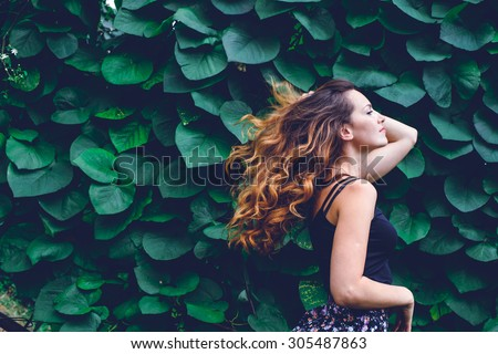 young woman, against background of summer green park, green leaves. Running girl with beautiful curly hair - stock photo