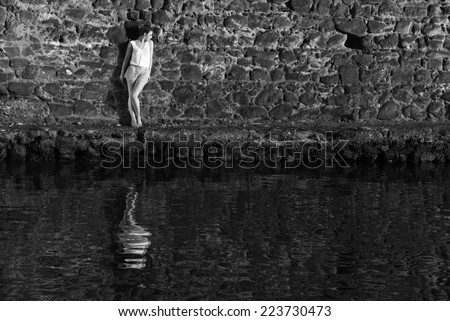 Young woman against the wall with reflection in the water - stock photo