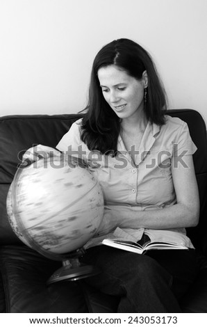 Young woman (age 30) search and examining the Globe  at home. Concept photo travel and education (BW) - stock photo