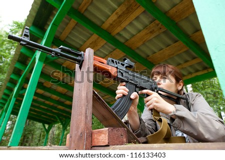 Young woman aiming at a target and shooting an automatic rifle for strikeball. Focus on the rifle. - stock photo