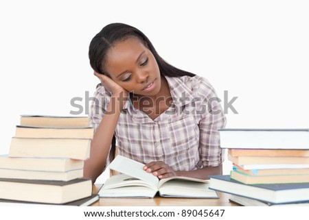 Young woman almost falling asleep while reading against a white background - stock photo