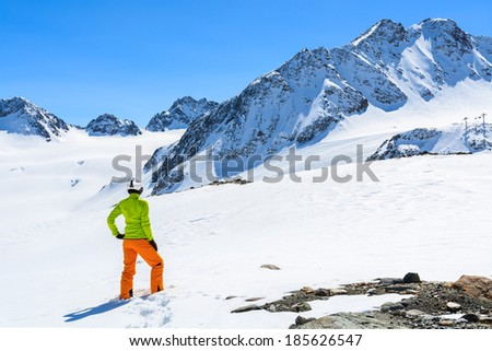 Young woman alpine skier in orange pants and green jacket stands in fresh snow on Pitztal Glacier in Austrian Alps - stock photo