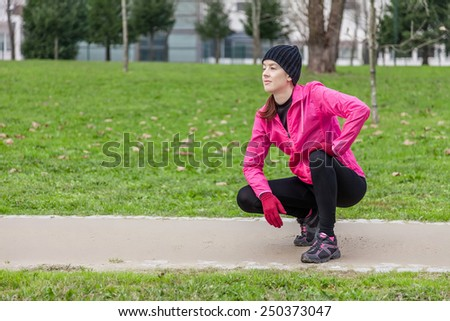Young woman analyzing the track before running on a cold winter day in an urban park. - stock photo
