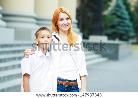 Young woman and at her son near school - stock photo