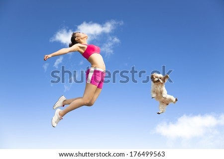 young woman and dog jumping in the sky - stock photo